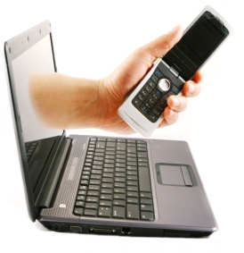 Image of hand with cell phone reaching out laptop screen