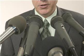 Speaker at podium with several microphones