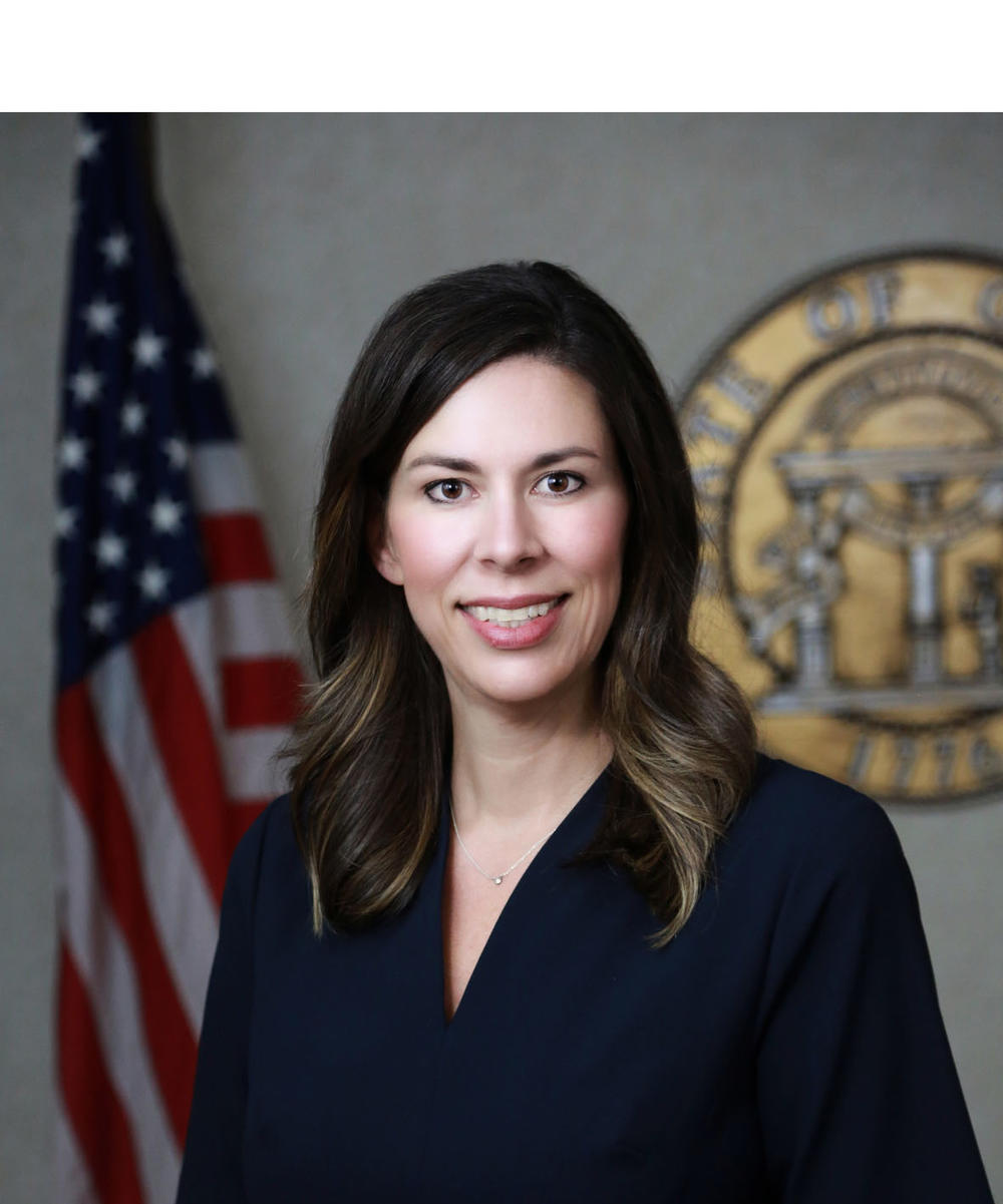 Professional headshot of a woman in front of the American flag and the official Seal of Georgia.