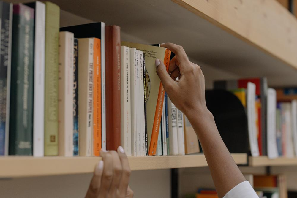 A woman's right hand reaches to pull a book from a library shelf.